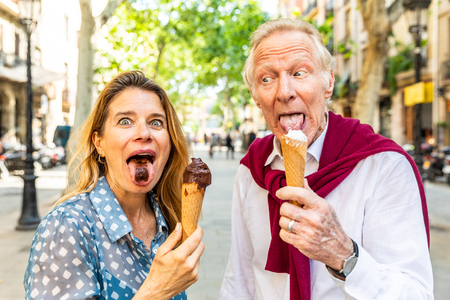 Foto de Senior couple eating ice cream and having fun in Barcelona. Adult woman and man making funny faces and grimacing while enjoying a fresh ice cream on a hot summer day in Spain. Summer and food concepts - Imagen libre de derechos