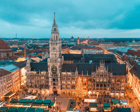 Foto de Munich Rathaus and main square with Christmas tree and decorations at night. Bavarian capital city during Christmas time with markets and lights, aerial view, toned image - Imagen libre de derechos