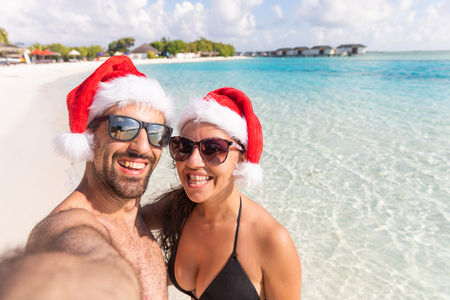 Smiling couple with Christmas Santa hat taking a selfie at seaside. Holiday tropical destination postcard for holidays season with xmas hats. Happy man and woman looking at camera.