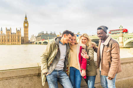 Foto de Happy multiracial friends group using smartphone in London. Mixed race millennials people lifestyle concept. Friends sharing trip on social network. Big ben and Westminster parliament on background. - Imagen libre de derechos