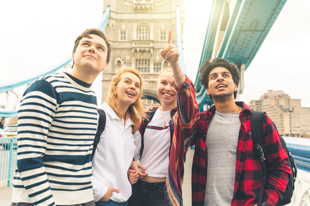 Photo pour Happy students on Tower Bridge in London during school trip - Multiracial group of teenagers best friends enjoying time together visiting the city - Lifestyle and tourism in London - image libre de droit