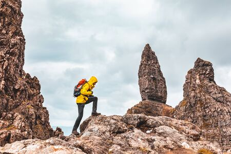 Photo pour Man hiking in Scotland, Isle of Skye at the Old Man of Storr - Hiker climbing on rocks with the famous rock of the Isle of Skye on a cloudy  day - Filter applied, travel and adventure concepts - image libre de droit