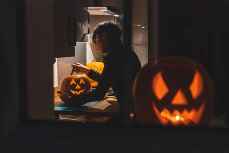 Foto de Woman carving pumpkin for Halloween night - View through the window of a young woman in the kitchen preparing pumpkins for the scary night - holidays, culture and lifestyle in UK and United States - Imagen libre de derechos