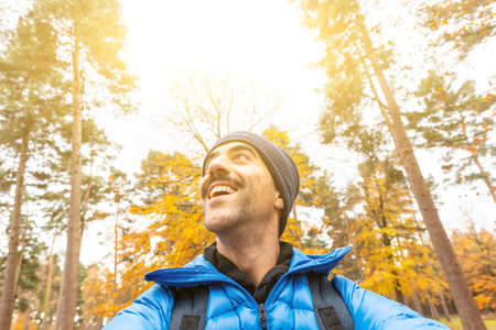 Photo pour Happy man taking a selfie in the wood with beautiful autumn vibes - Young man alone enjoying time in a remote forest away from city and busy life - lifestyle and nature - image libre de droit