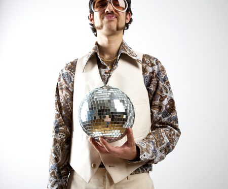 Photo for Portrait of a retro man in a 1970s leisure suit and sunglasses holding a disco ball - mirror ball - Royalty Free Image