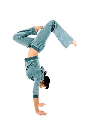 An isolated view of an agile gymnast doing a graceful handstand. White background