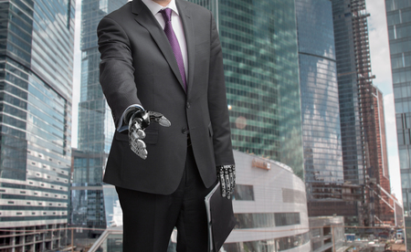 A robot businessman with open hand ready to seal a deal against modern skyscrapers on background. Focus on a hand.の写真素材