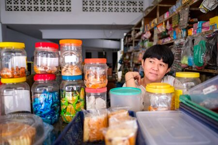 Photo for Asian Indonesian women in front of small local family-owned business store, locally called warung. Location is in Tasikmalaya, Indonesia. Selective Focus. - Royalty Free Image