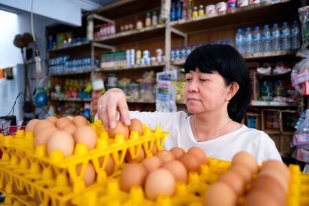 Photo pour Asian Indonesian women arranging eggs inside small local family-owned business store, or locally called warung. Location is in Tasikmalaya, Indonesia. Selective Focus. - image libre de droit