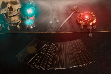 Tarot card, skull and crystal ball on the table with smoke under candlelight. Dark tone.