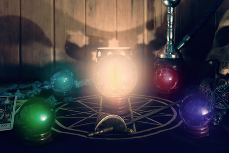 View of crystal ball on the table. Dark tone.