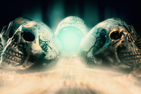 View of crystal ball and skull with smoke on the table. Dark tone. Shallow depth of field.