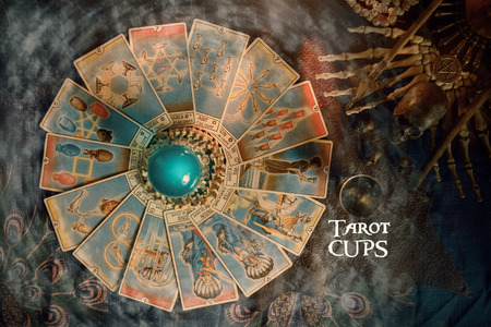 View of Tarot card (Minor arcana) and crystal ball on the table. Tarot of cups.
