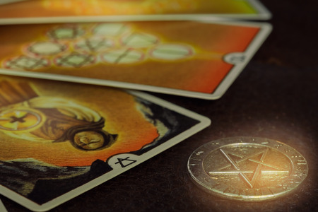 View of pentacle coin and Tarot card (Minor arcana) on the table. Dark tone.