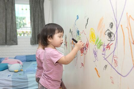 Photo pour little baby boy and girl drawing with crayon color on the wall - image libre de droit