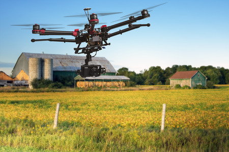 Photo pour A flying helicopter with raised landing gears and a camera with blurred crop field and farm structures on a background highlighted by a sunset - image libre de droit