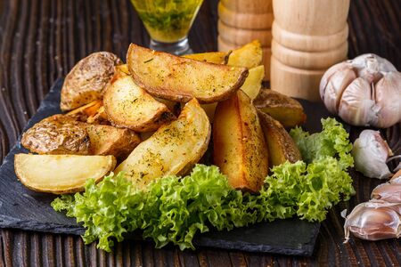 Photo pour Potato wedges baked in their skins with lettuce on wooden background. A dish on a stoyn plate with a sauce in a glass pial. - image libre de droit