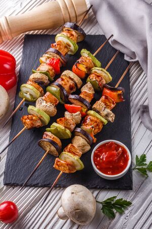Photo pour chicken kebabs with vegetables and mushrooms on a rustic background. - image libre de droit