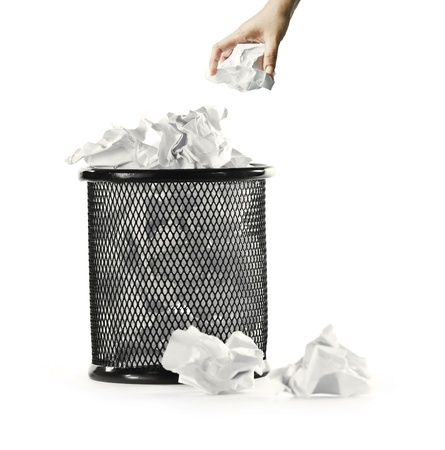 hand with paper and garbage bin over white