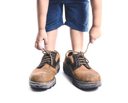 Photo for kid in big shoes on white background - Royalty Free Image