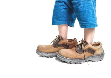 Foto de kid in big shoes on white background - Imagen libre de derechos