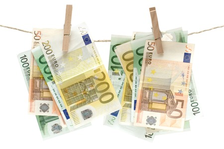 Several different euro banknotes held by a clothesline. Isolated on a white background.