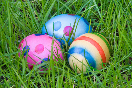 Colorful eggs hidden in green grass.