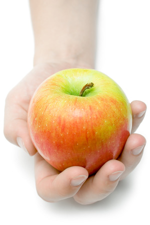 Female hand offering a colorful apple. Isolated on a white background.