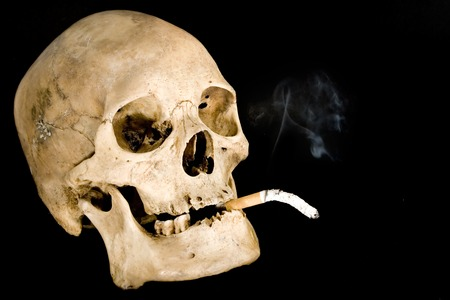 Human skull smoking. Isolated on a black background.