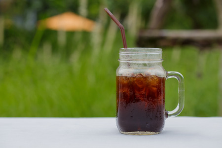 An ice Americano coffee on the white table in the garden.