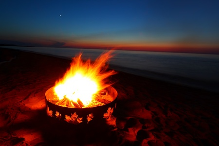 Campfire and beautiful sunset along the beautiful beach of Lake Superior in northern Michigan