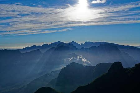 Photo pour A distant landscape shot of green hills and mountains under a sunny sky - image libre de droit