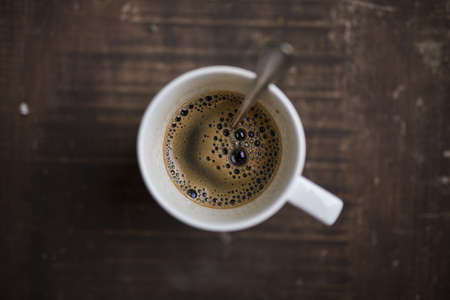 Photo pour Coffee in a white cup and a spoon on a wooden background shot from above - image libre de droit