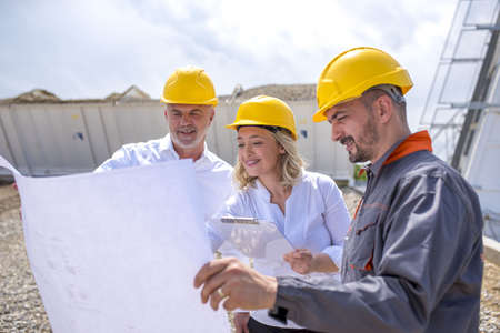 Photo for A group of construction workers looking at the plans and documents under the sunlight - Royalty Free Image