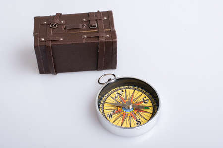 A high angle shot of a compass and a valise isolated on a white background