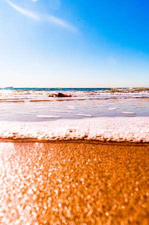 Photo pour A sunny scenery of a beautiful sandy beach on a blue seascape background - image libre de droit