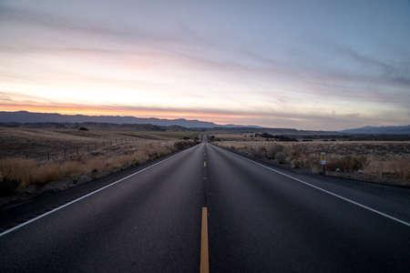Foto für A shot of a highway road surrounded by dried grass fields under a sky during sunset - Lizenzfreies Bild