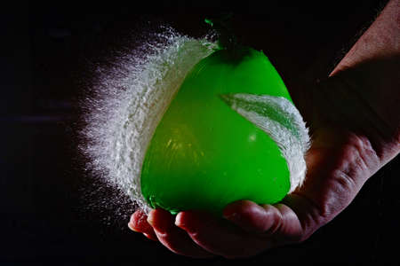 Photo pour A slow motion shot of a person popping a balloon with a black background - image libre de droit