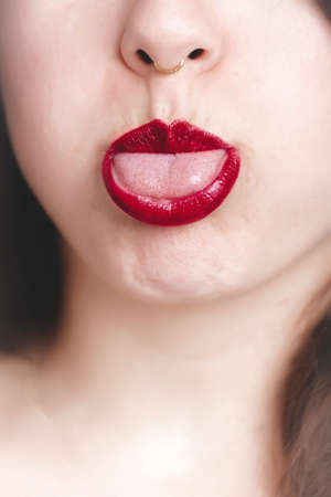 Photo pour A vertical closeup shot of a female with red lipstick showing her tongue - great for a fashion blog post - image libre de droit