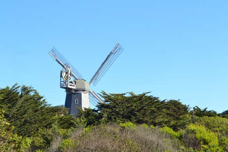 Photo for A grey windmill at Ocean Beach surrounded by greenery under a blue sky in San Francisco - Royalty Free Image