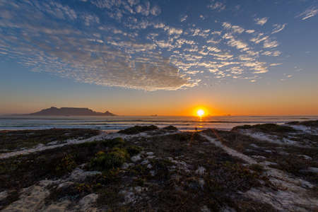 Photo pour A beautiful shot of the sunset over the shore of the famous Table mountain in Cape Town, South Africa - image libre de droit
