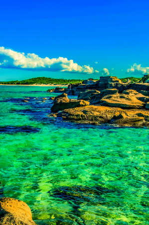 Photo pour A vertical shot of rock formations in the middle of the sea with extraordinary colors - image libre de droit