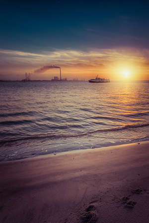 Photo pour A vertical shot of a beautiful sunrise at the beach creating the perfect scenery for morning walks at the shore - image libre de droit