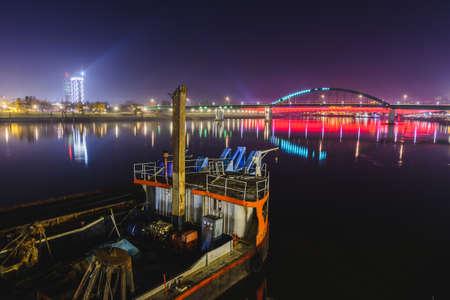 Foto für View at the part of an old ship, old railway bridge and distant city lights at night. - Lizenzfreies Bild