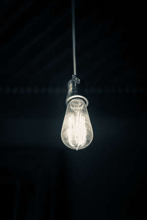 Photo for A vertical shot of a hanging turned on light bulb with a dark background - Royalty Free Image