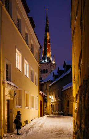 TALLINN, ESTONIA - Nov 08, 2016: St. Olaf's Church towering over Tallinn Old Town, Estonia, on a snowy winter evening