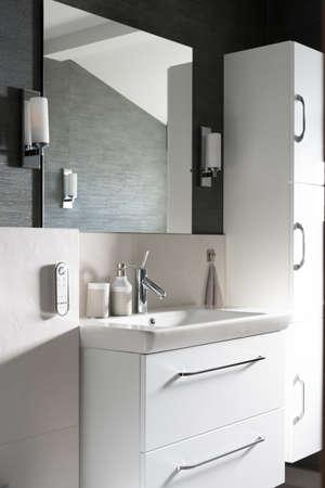 Photo pour A vertical shot of a bathroom with a mirror and white furniture - image libre de droit