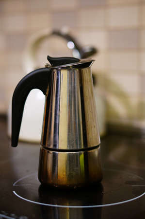 Photo for A vertical closeup shot of a metallic kettle placed on the electric stove with a blurred background - Royalty Free Image