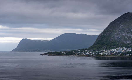 A mesmerizing view of a coastal line with mountains in background under a cloudy sky in Akureyri, Iceland
