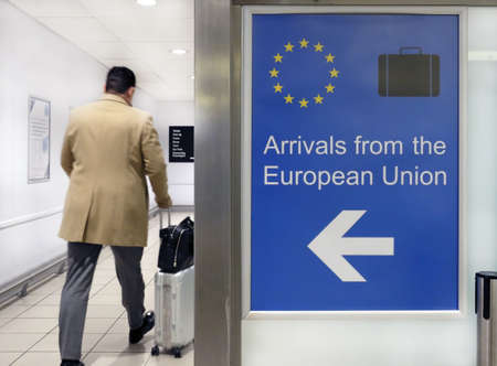 Photo pour A wide angle shot of an airport sign welcoming people arriving from the European Union next to a person - image libre de droit